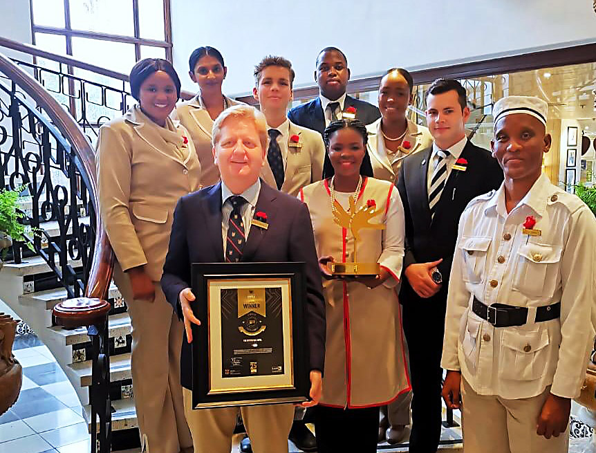 FEATURED IMAGE: Wayne Coetzer (front left), outgoing general manager of The Oyster Box, and staff with the hotel's fifth Lilizela Tourism Award for best five star hotel in the country.